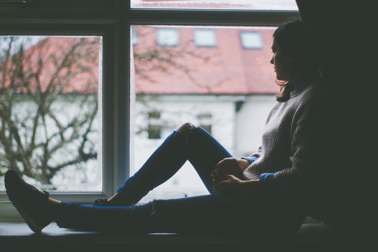 illustratie: fata stă în geam odihnind picioarele lungi